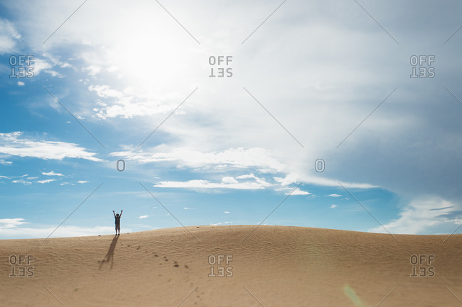 Kid standing on the ridge of a sand dune