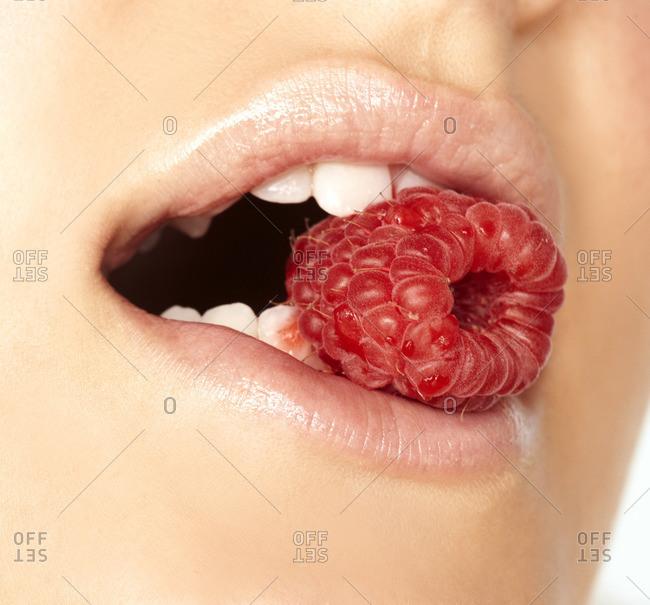 Woman eating a ripe raspberry
