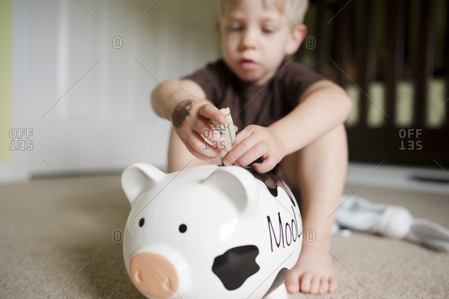 Little boy putting a twenty dollar bill into a piggy bank