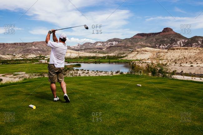 A golfer tees off at a golf resort, Lajitas, Texas