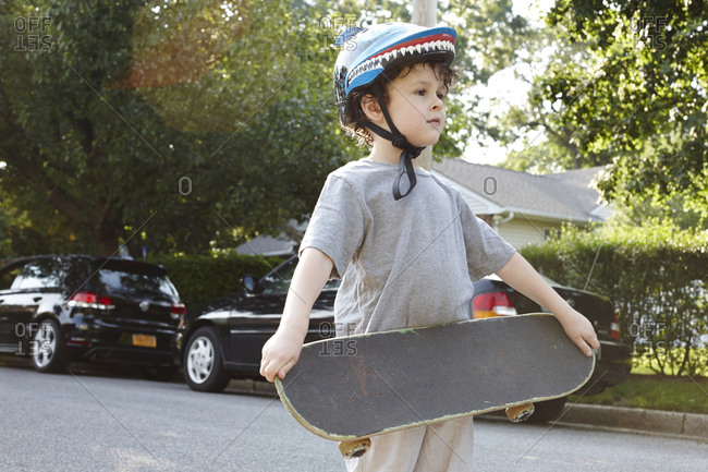 Young boy holding a skateboard in a street