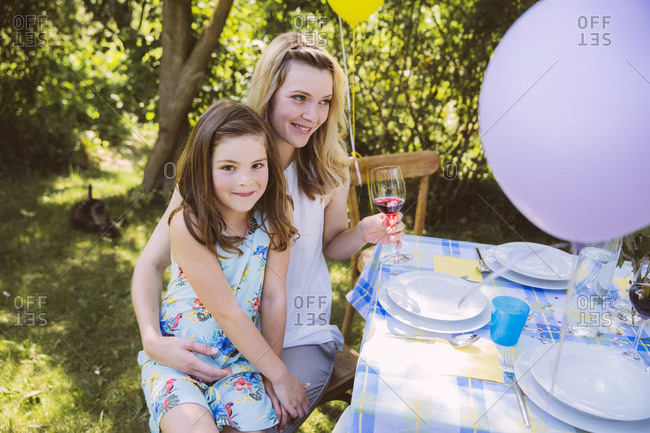 Daughter sitting on mother\'s lap at garden party table