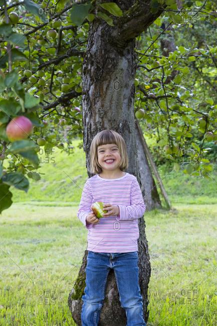 Portrait of little girl leaning on an apple tree