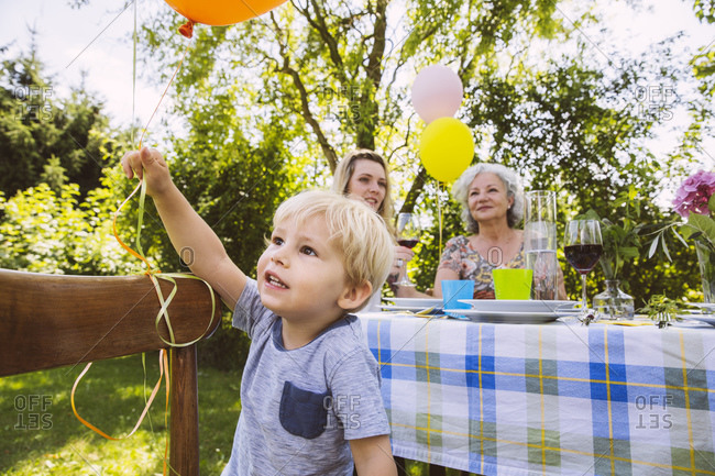 Boy at table with family of three generations in garden