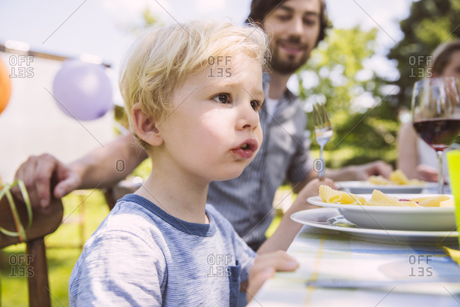 Boy eating pasta with family at garden table