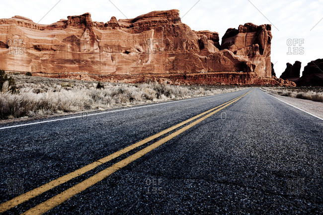 Road by sandstone mountains in Arches National Park, Utah