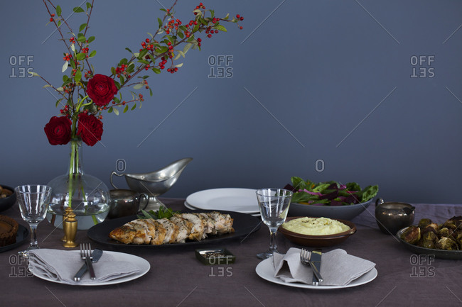 Table set for thanksgiving with a bouquet of red roses