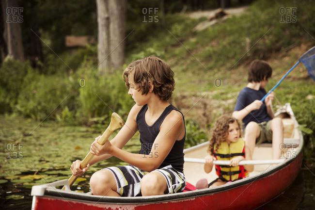 Children canoeing on lake - Offset