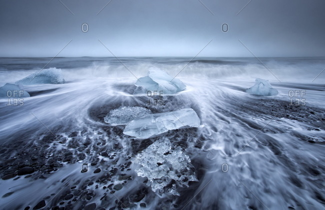 Jokulsa Beach on a stormy day with icebergs washed onto the black volcanic sand beach, Iceland