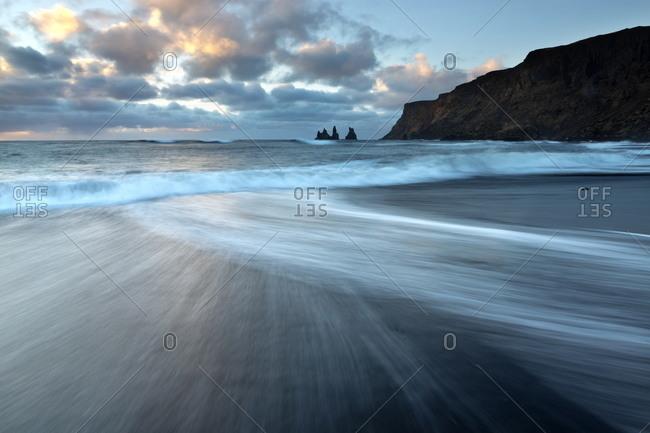 Looking towards the sea stacks of Reynisdrangar at sunrise from the black volcanic sand beach at Vik i Myrdal, Iceland