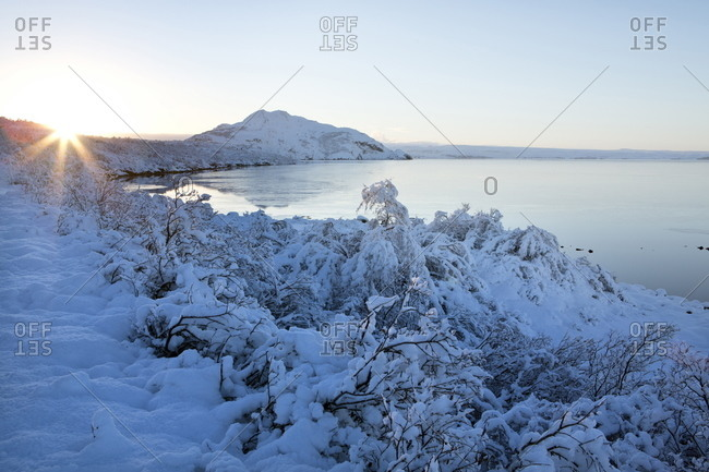 View towards Pingvallavatn Lake on a clear winter's afternoon with the shore and distant mountains covered in snow, Iceland