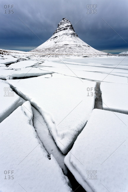 Winter view over slabs of broken lake ice covered in snow towards Kirkjufell (Church Mountain), Iceland
