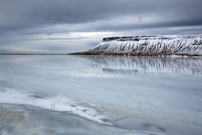 Winter view over a frozen lake towards snow-covered headland near Grundarfjordur, Iceland