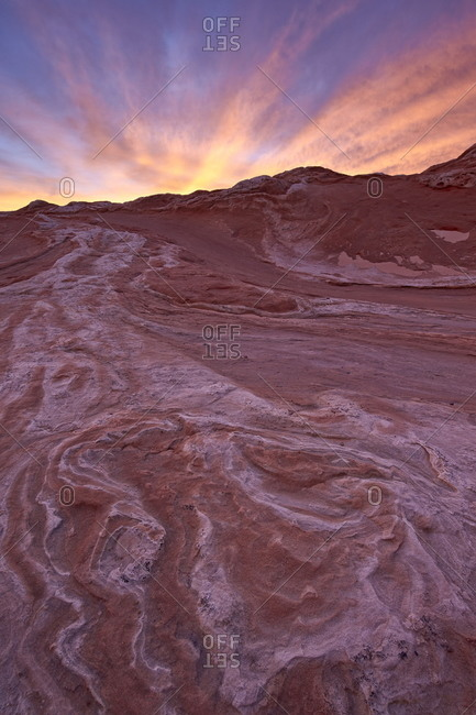 Brilliant orange clouds at sunset over red and white sandstone