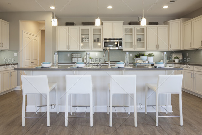 White bar stools at breakfast bar in domestic kitchen