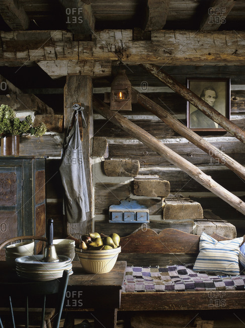 Rustic stairs descending into kitchen area in restored log home