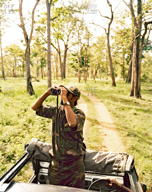 A guide looking through binoculars at the Bandipur Tiger Reserve, near Bangalore, India