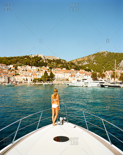 Woman standing on the prow of a yacht in the harbor of Hvar, Croatia
