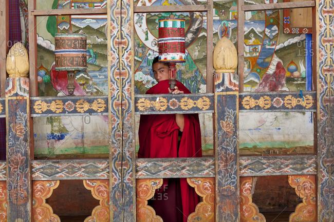 Tongsa, Bhutan - October 6, 2011: Young monk touches prayer wheel behind painted wooden frames, Bhutan