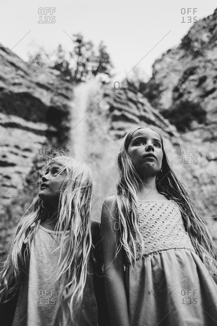 Two girls standing at the foot of a waterfall
