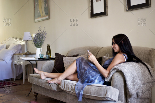 Young woman reading smart phone on couch
