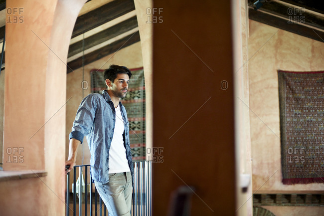 Man leaning against railing over grand hall