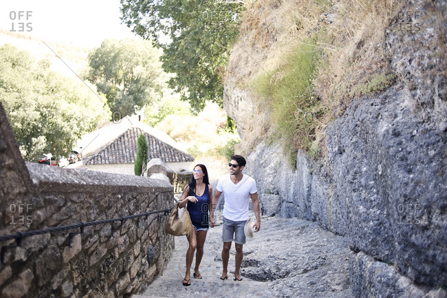 Couple walking up steep stairway in quaint village