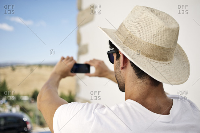 Man taking picture with phone in quaint village