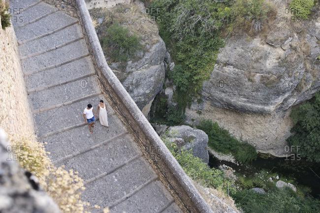 Couple walking along ancient steps in quaint village