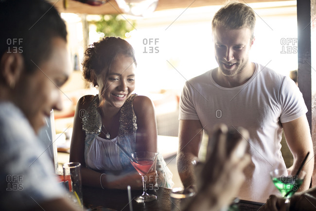 Bartender serving drinks to a young couple in a bar