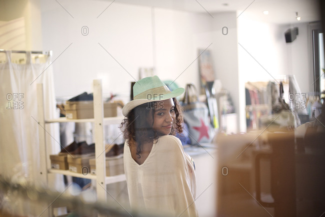 Young woman trying a hat in a clothing store