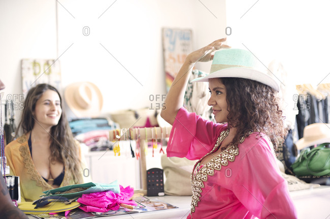 Young woman posing in a hat in a clothing store