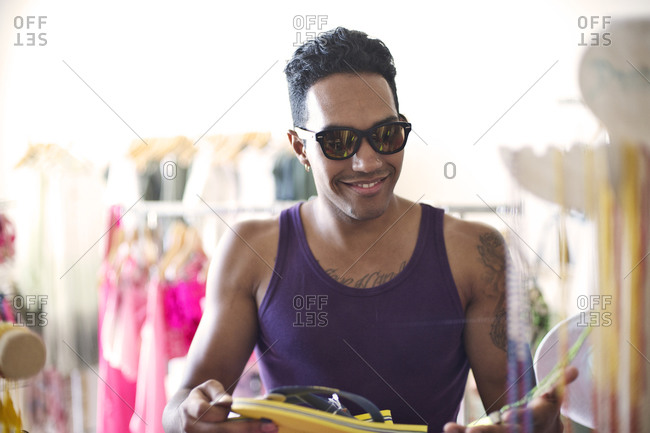 Young man in a clothing store trying sunglasses