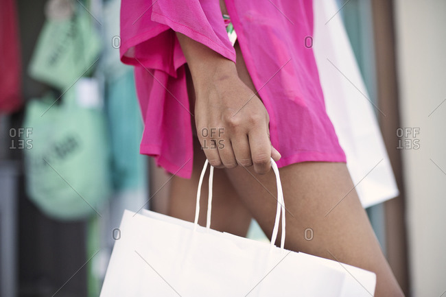 Mid section view of woman walking with paper bag