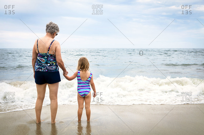 Rearview of girl and grandmother watching incoming waves on beach