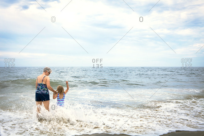Young girl enjoys the waves with her grandmother