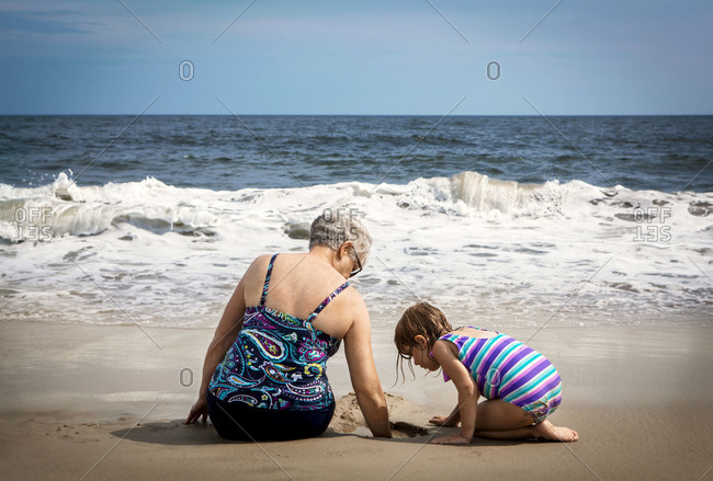 Young girl and her grandmother playing with sand on a beach