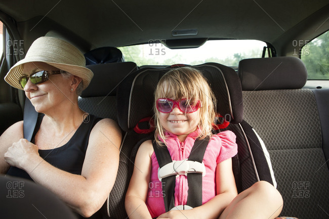 Young girl and grandmother sitting in the backseat of a car