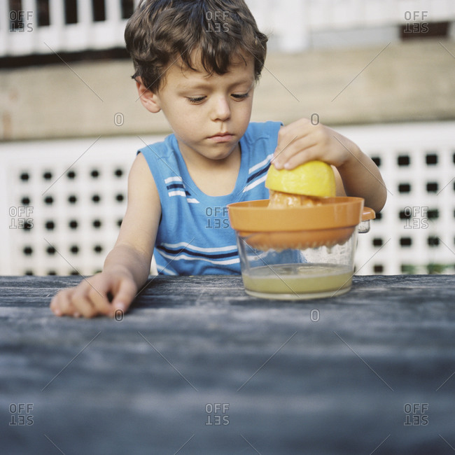 Young boy squeezing a lemon