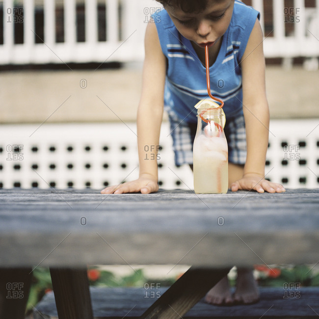 Young boy drinking lemonade from a bottle