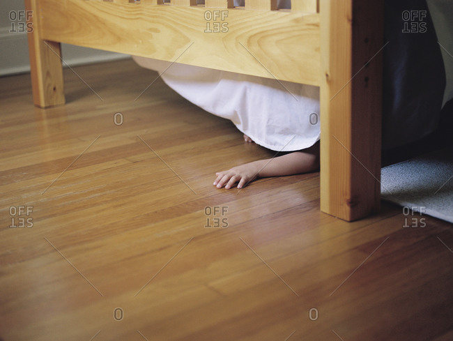 Child's arm poking out under a bed