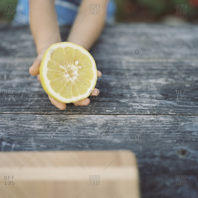 Child holding a halved lemon