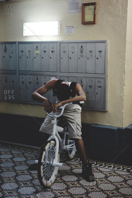 Teenager resting his head on the handlebar of his bike
