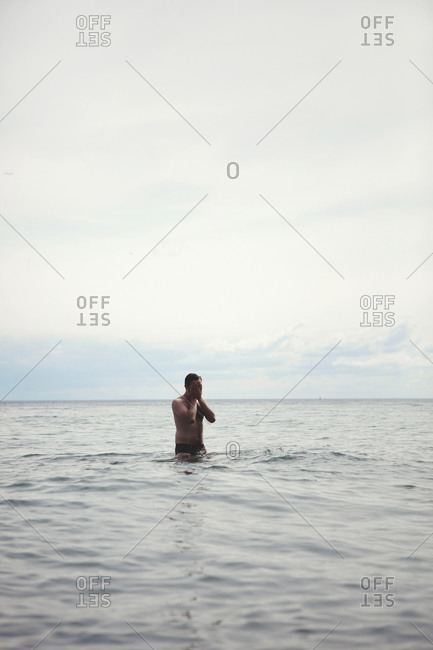 Man wiping water off his face in the ocean