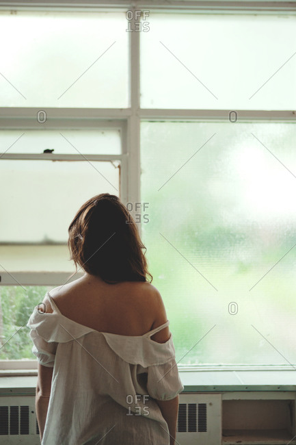 Back view of woman looking out the window