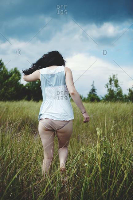 Back view of woman walking in a grass field in her underwear