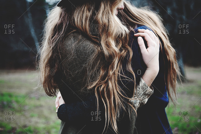 Mid section view of two long haired girls embracing on field