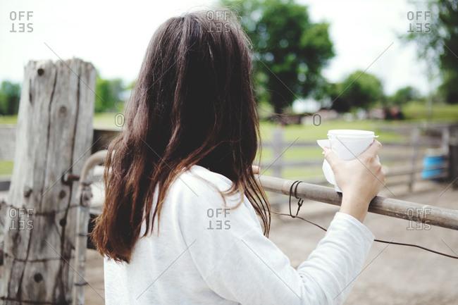 Brunette girl watching a cattle-pen