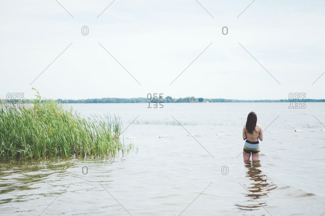Rear view of a brunette woman standing in the water