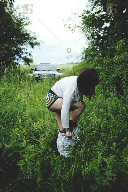 Woman getting dressed among bushes